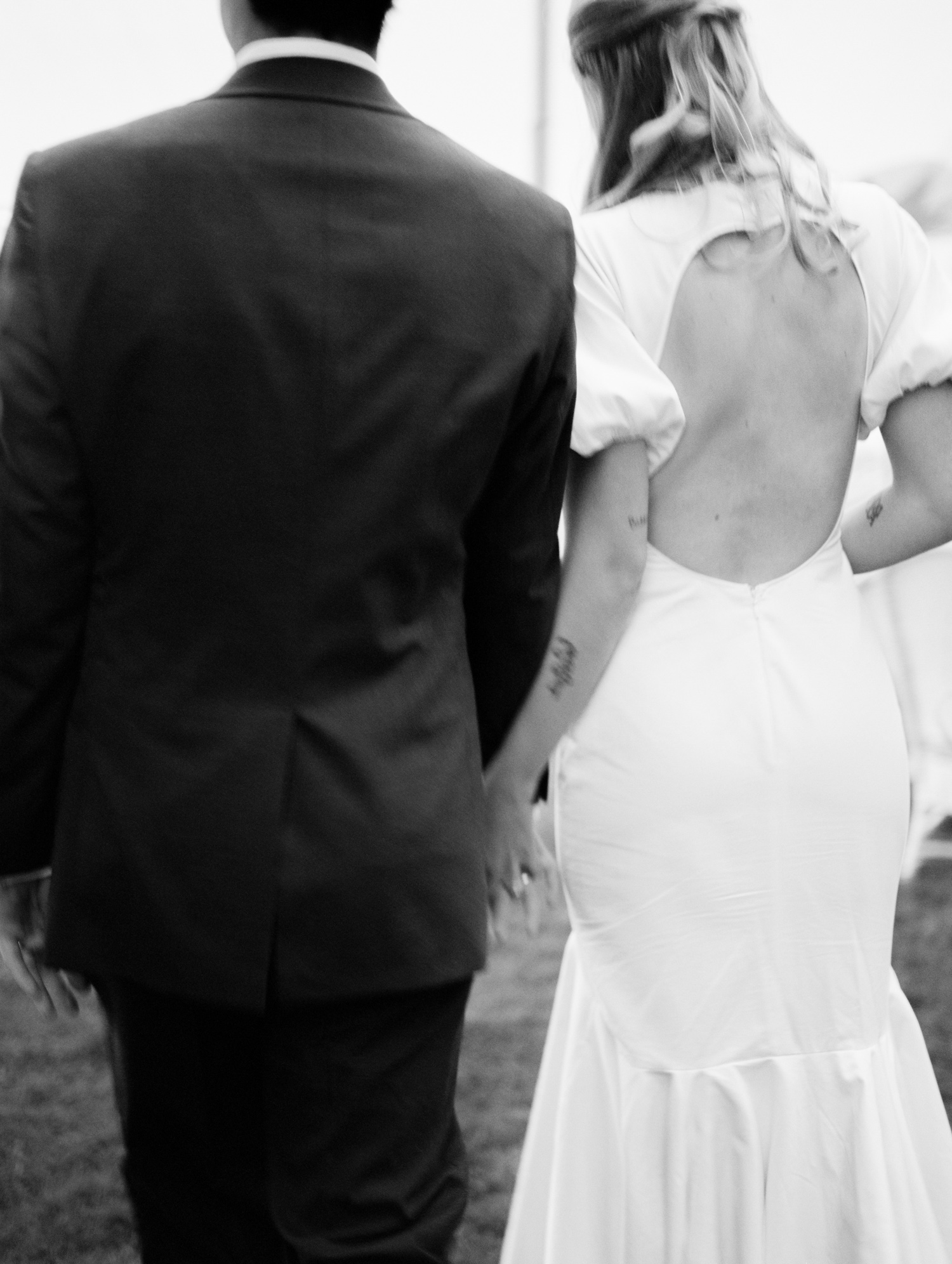 a soft black and white image showing movement of a wedding couple with tattoos holding hands