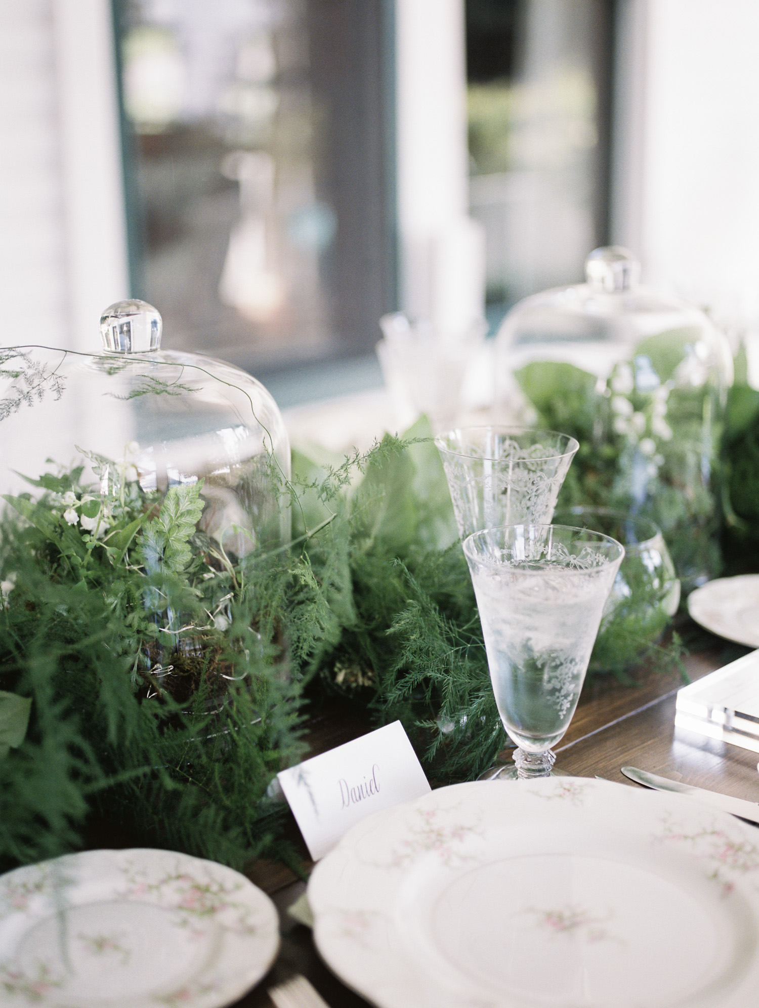 Vintage glassware and glass cloche centerpieces on a wedding dinner table in Michigan