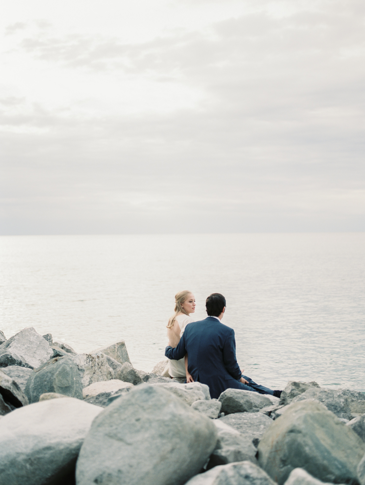 A bride and groom sit in front of Lake Michigan during their Petoskey wedding