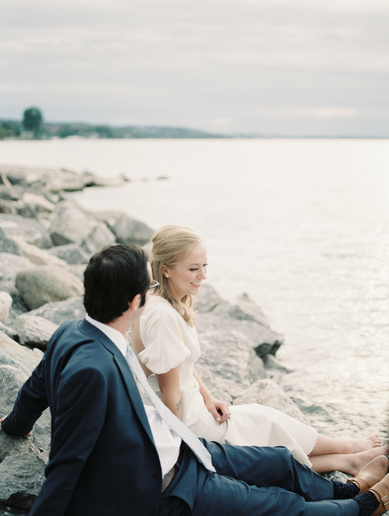 A couple relaxes on Lake Michigan on their wedding day in Petoskey