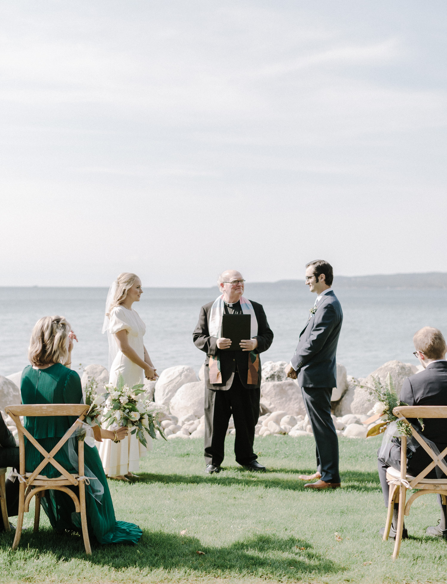 A small wedding ceremony on Lake Michigan with wood chairs in Petoskey, northern Michigan