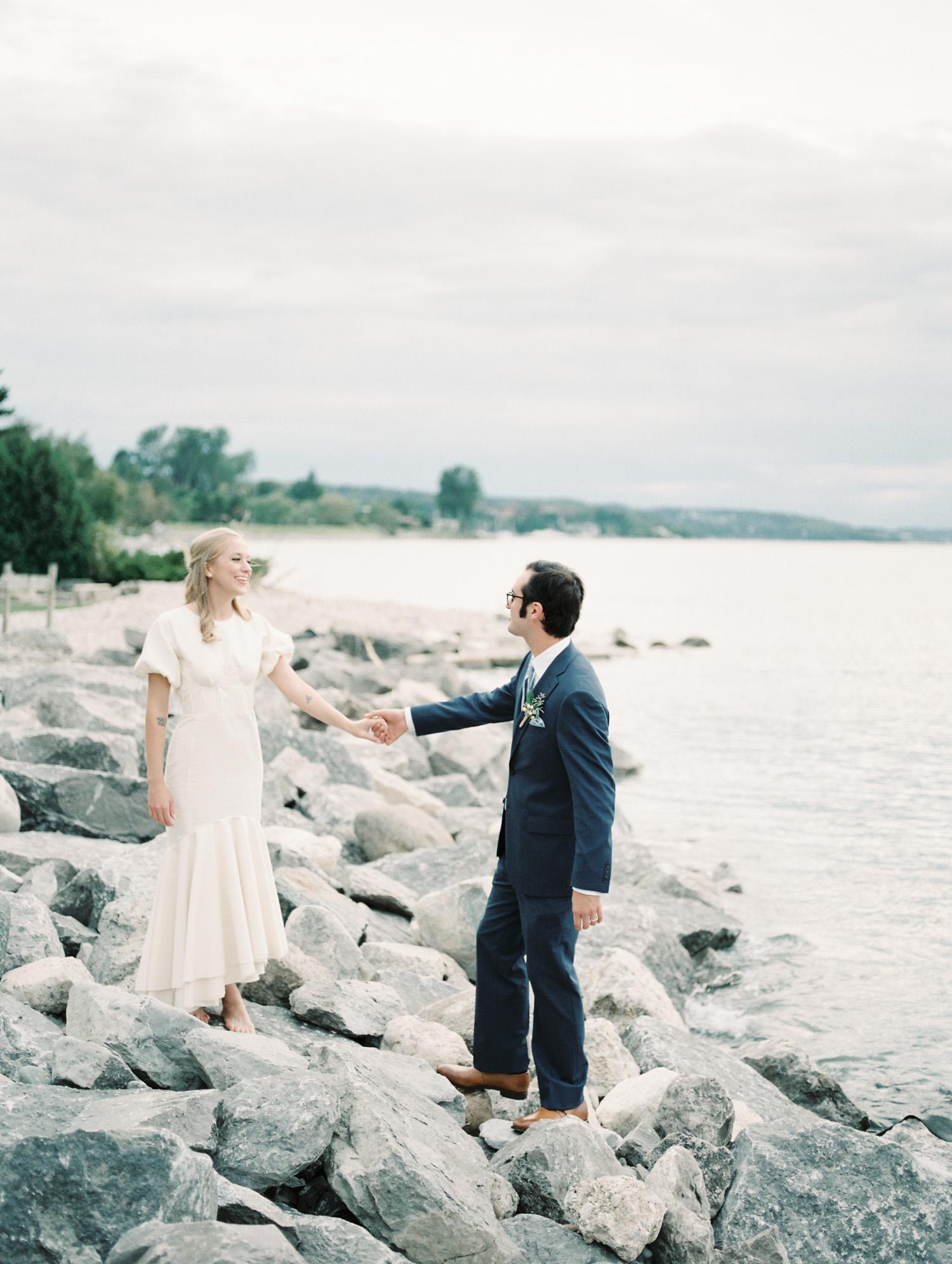 A wedding couple walks along rocks on Lake Michigan in Petoskey