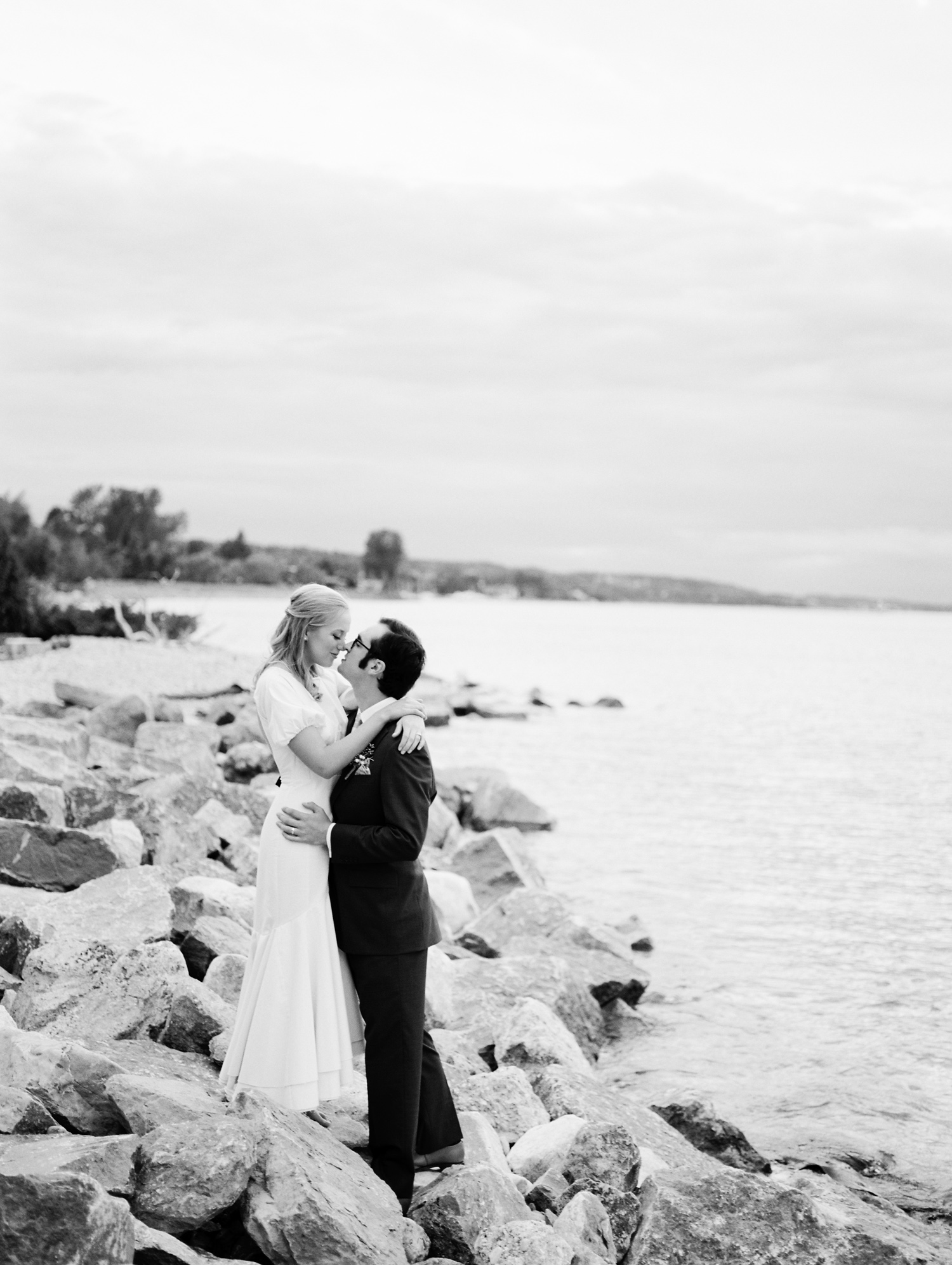 A bride and groom embrace on the coast of Lake Michigan during their Petoskey wedding