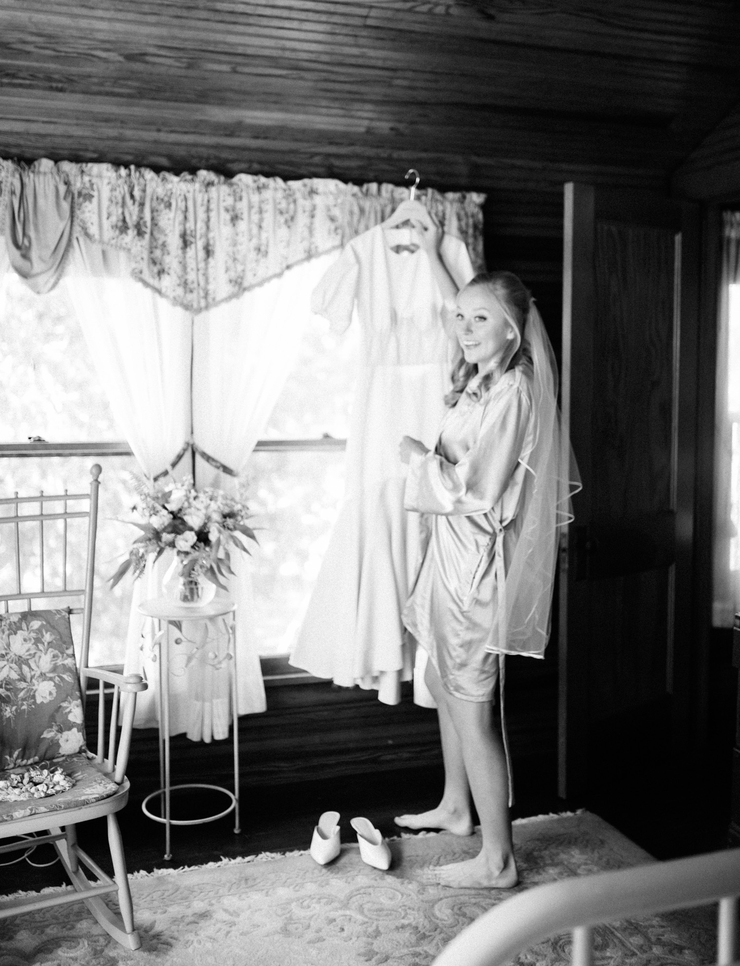 a smiling bride in a silk robe takes her gown off the hanger while preparing for her Northern Michigan wedding