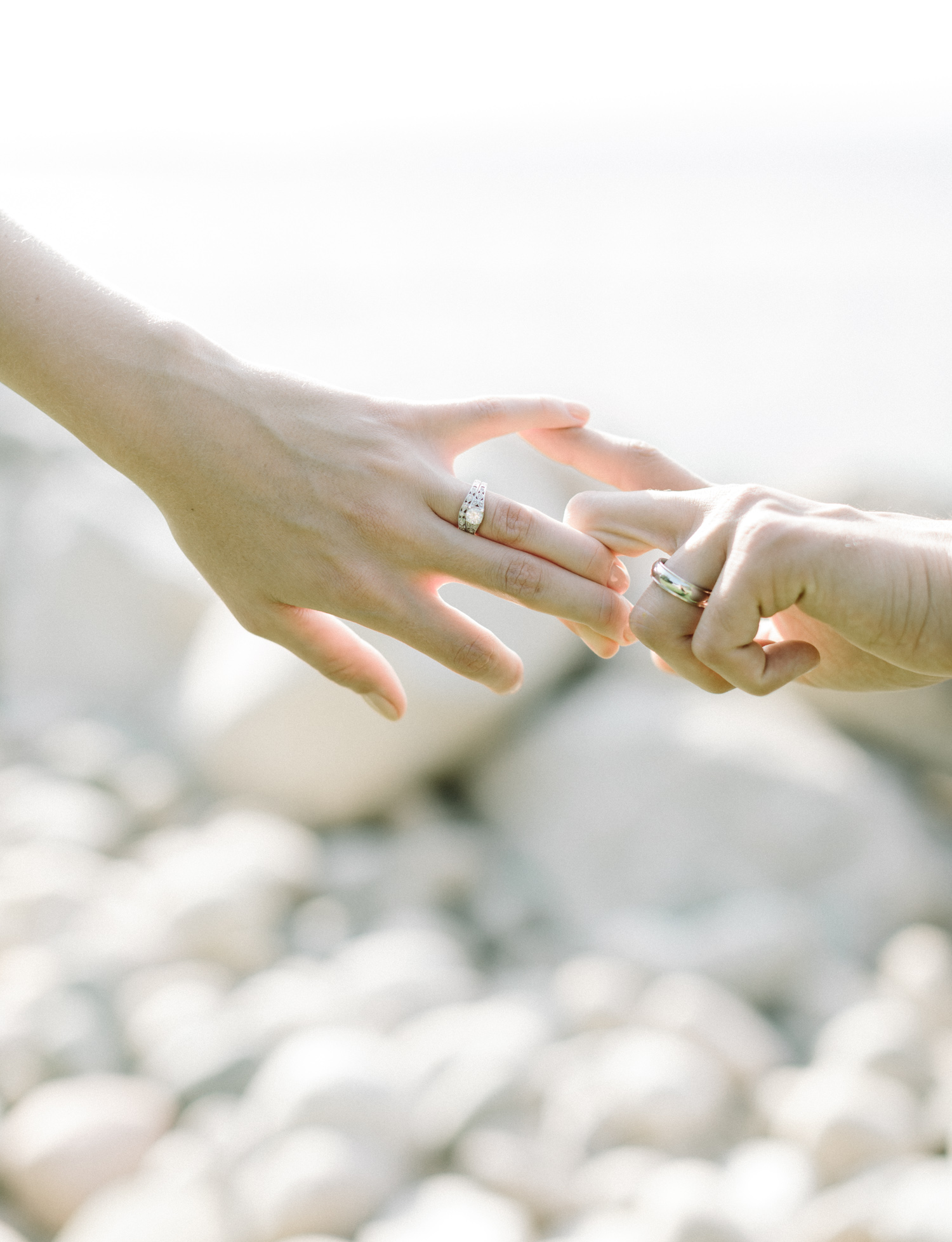 A couple wearing vintage white gold wedding rings holds hands in front of Lake Michigan