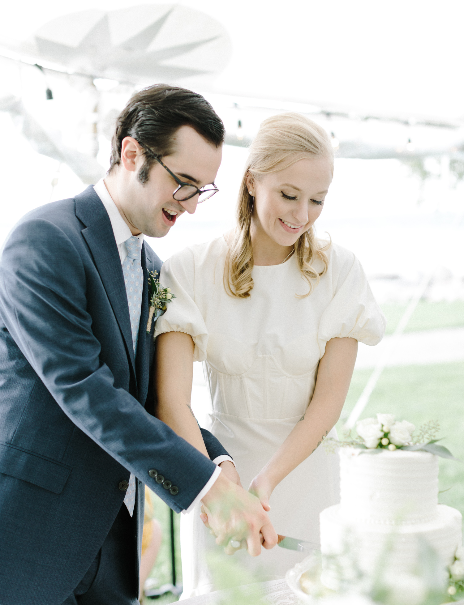 a couple laughs and smiles while cutting their wedding cake in Petoskey, Michigan