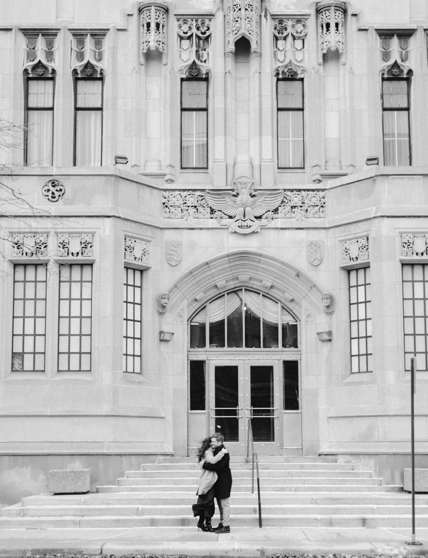 A windswept couple embraces outside the Masonic Temple in Detroit during their downtown engagement photos