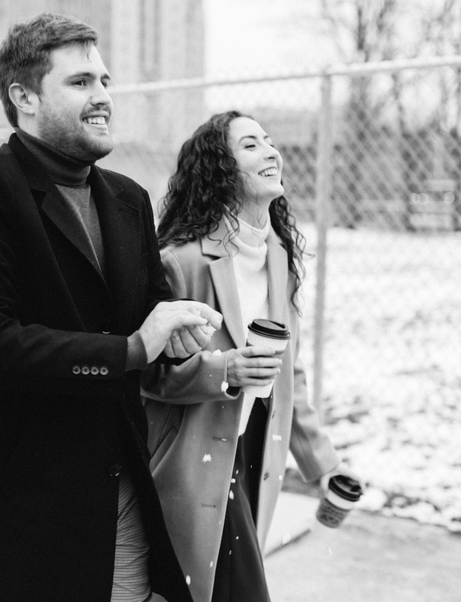 A couple laughs while walking down the street with coffee during their Detroit engagement photos
