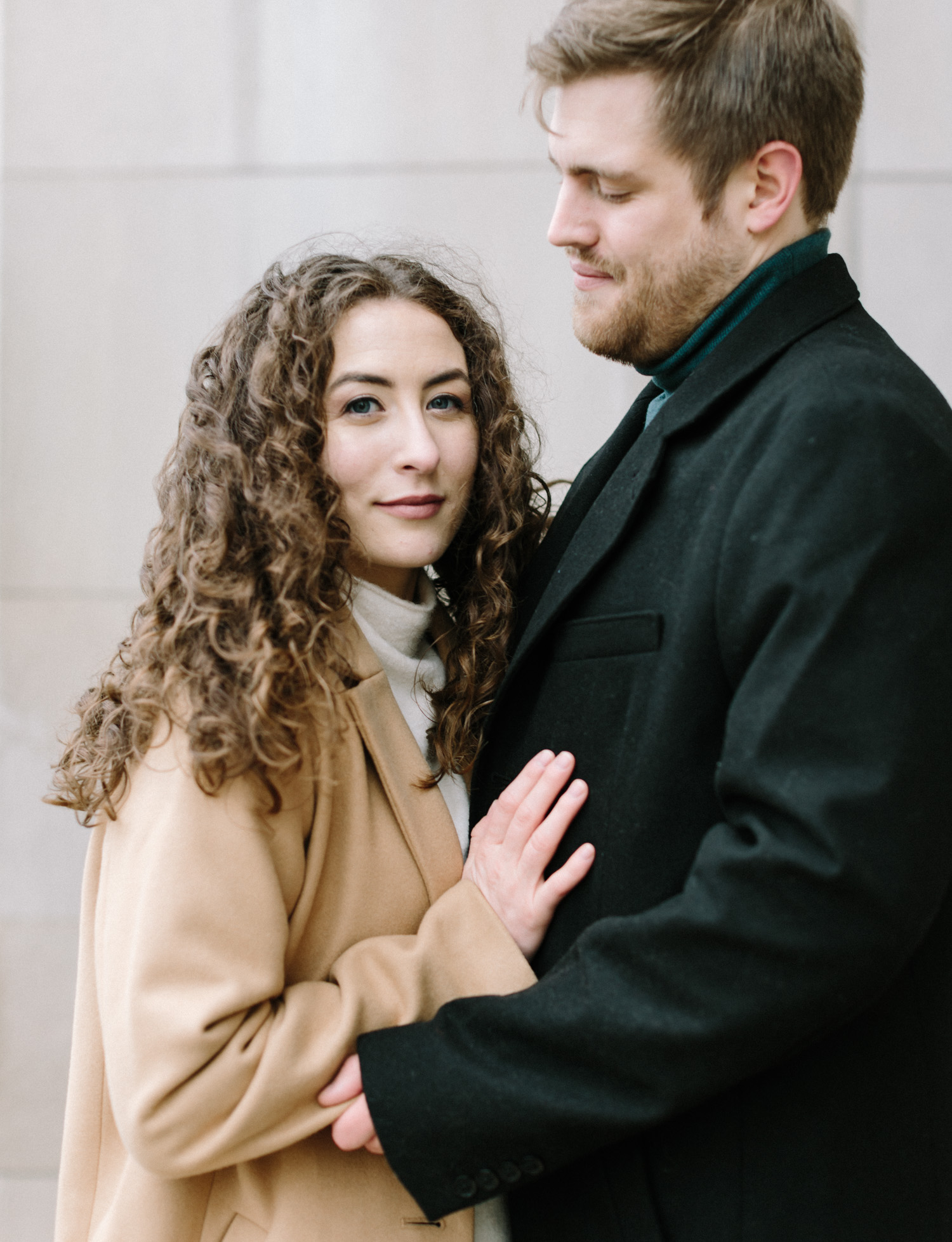 A woman with curly brown hair in a camel coat looks at the camera while embracing her love during their Detroit engagement photos at the masonic temple