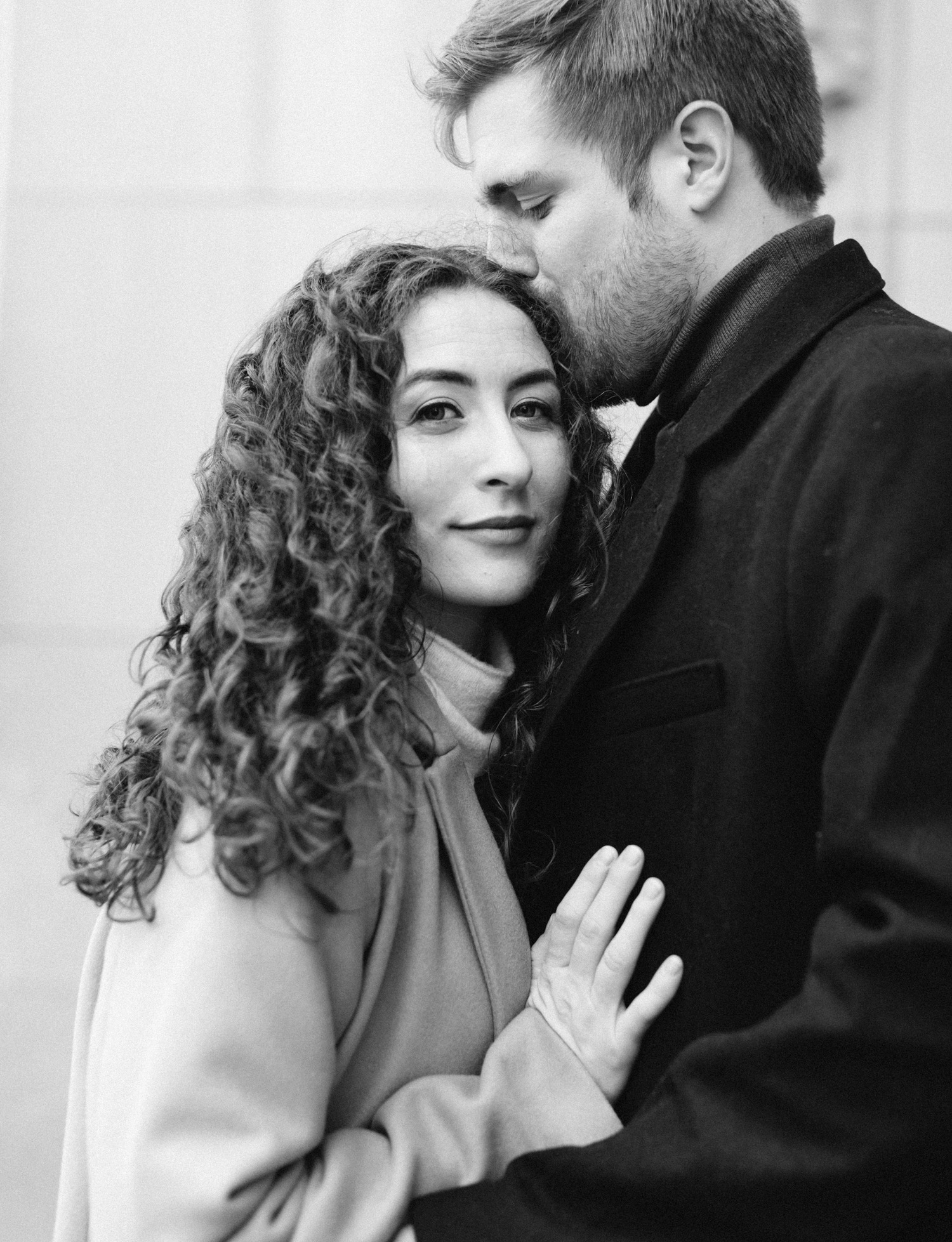 A woman with curly hair looks at the camera while embracing her love during their engagement session at the Masonic Temple in Detroit