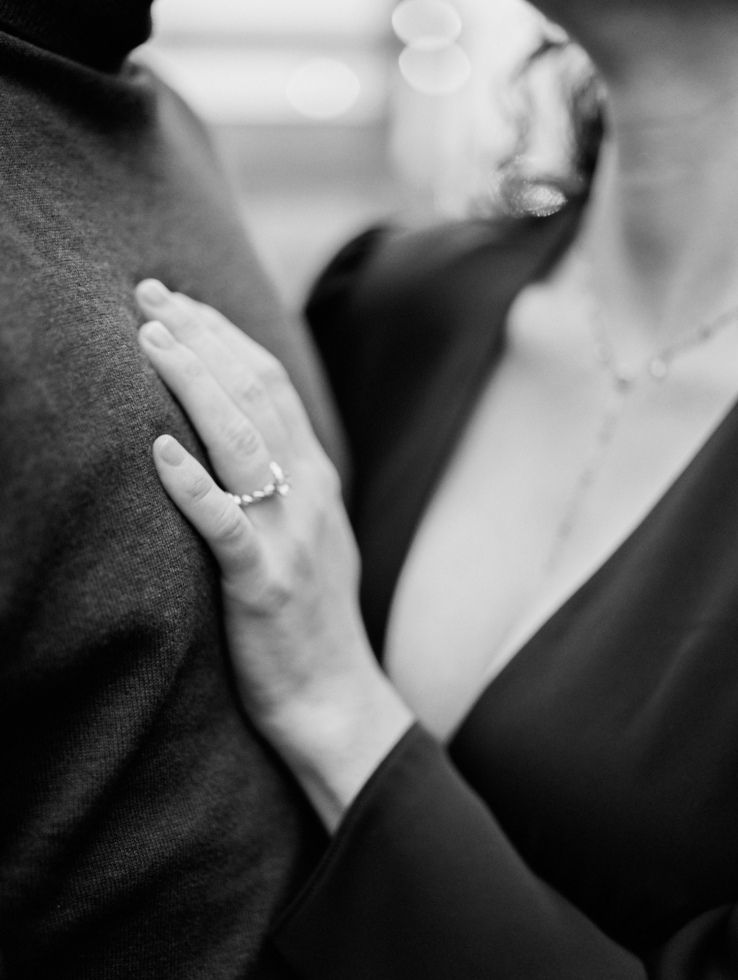 a woman's hand with an oval diamond engagement ring rests on her love's chest in soft focus