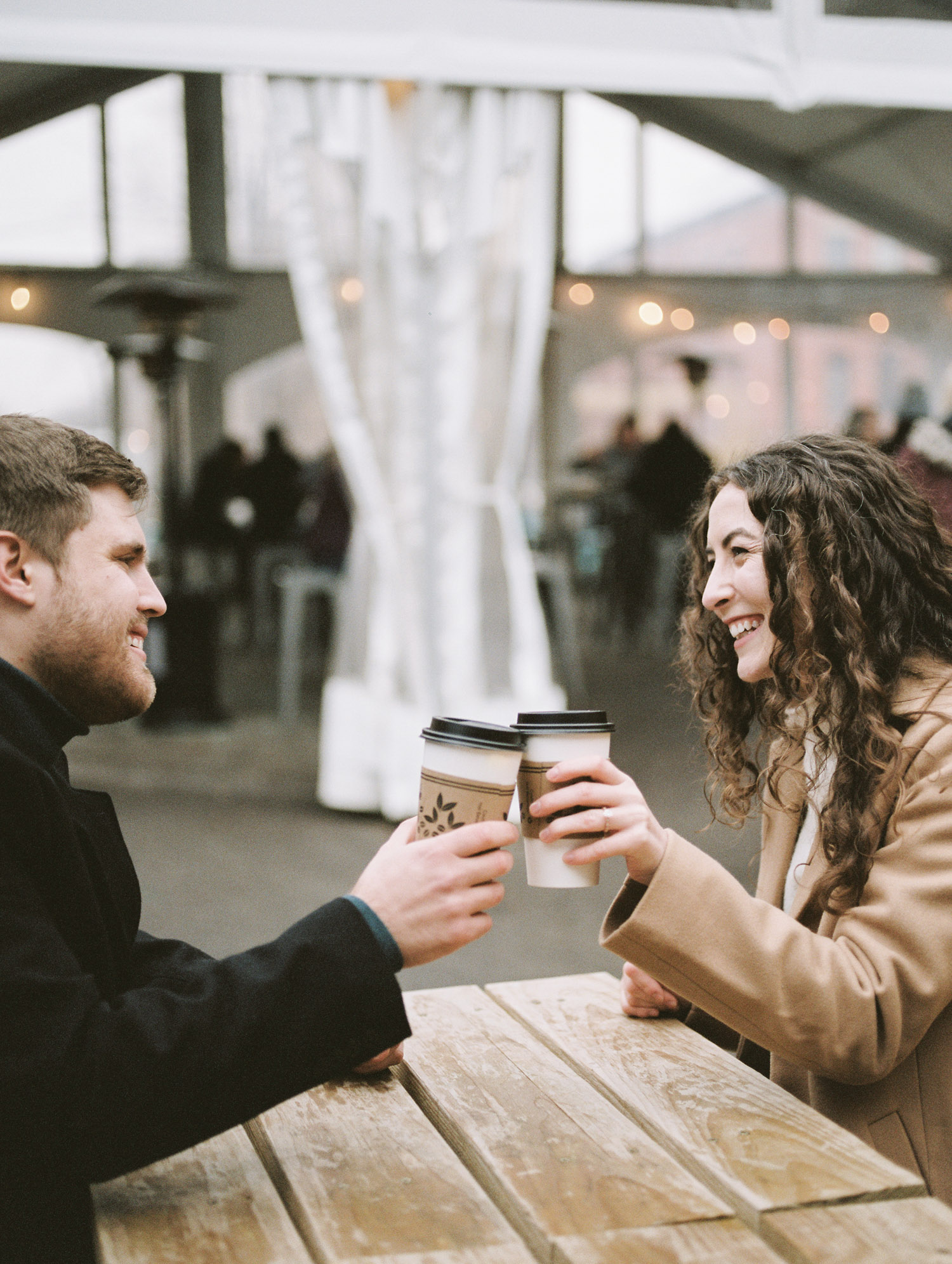 A couple toasts with coffee during their winter engagement photos in Detroit