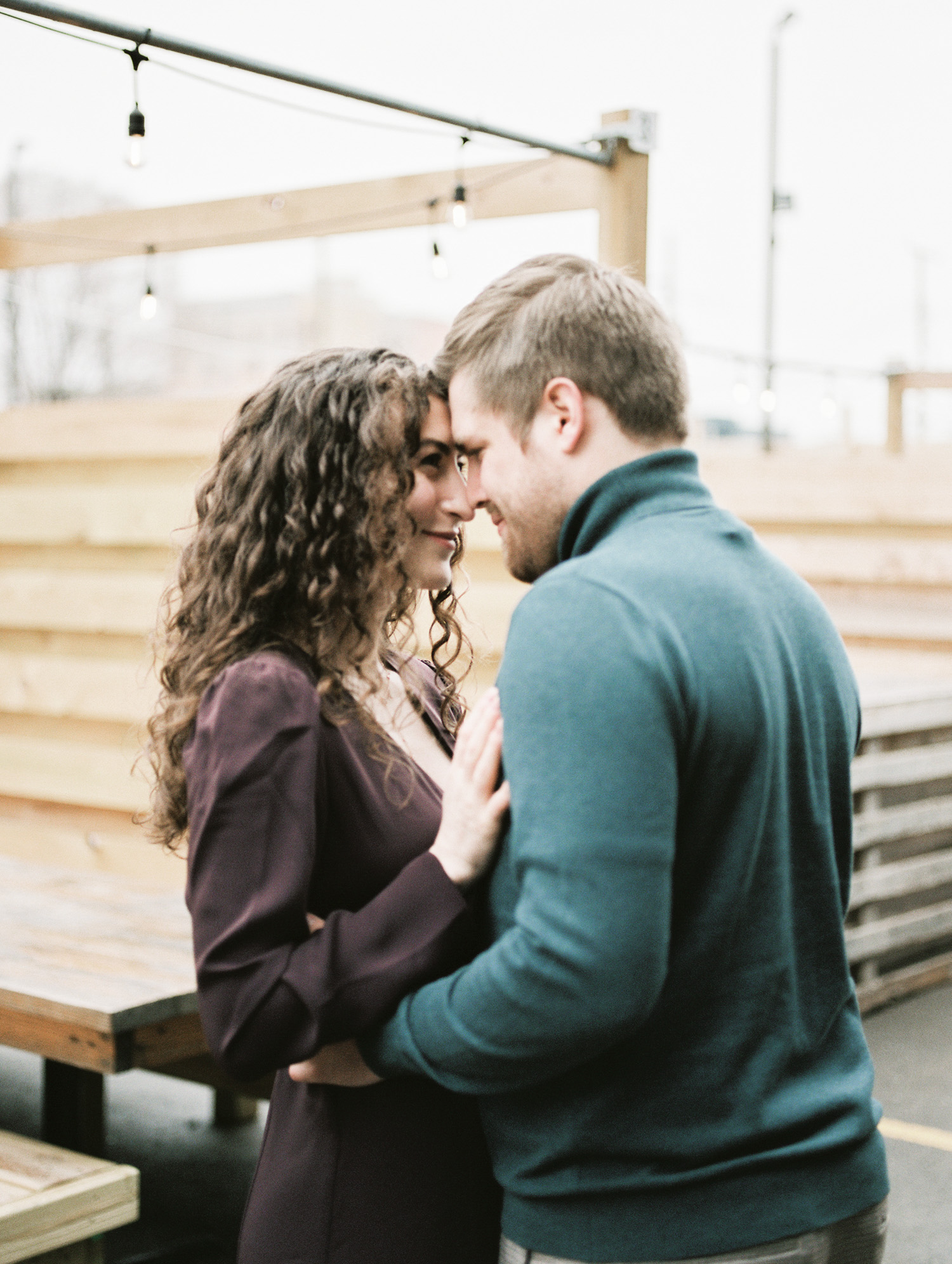 a couple embraces during their winter engagement photos in Detroit