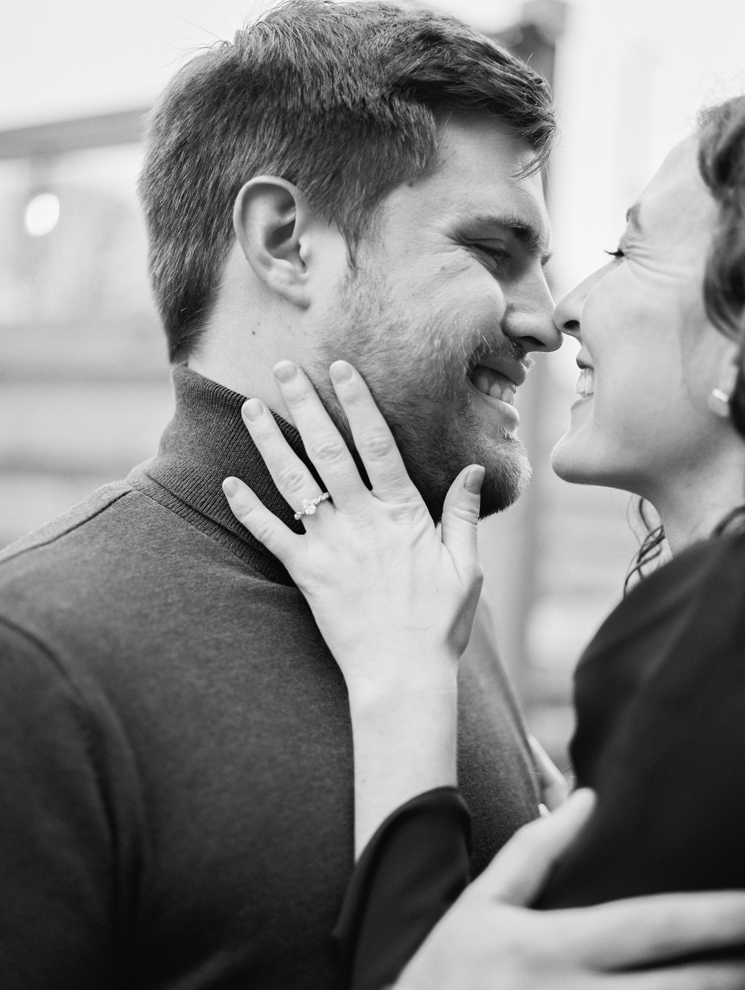 A woman with an oval diamond engagement ring smiles with her fiance during their Detroit engagement photos