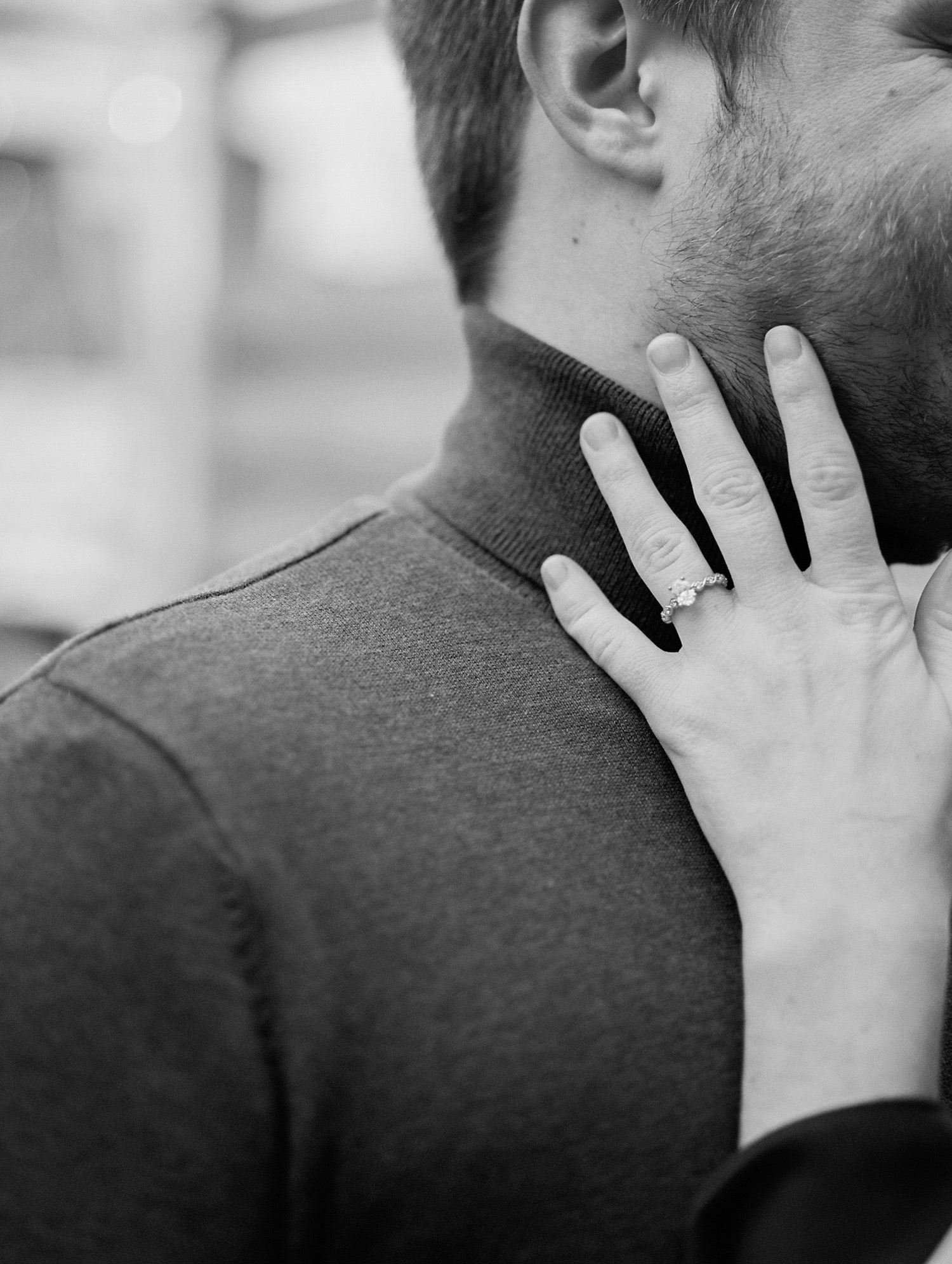 a woman's hand with an oval diamond engagement ring touching her love's neck during their engagement photos in Michigan
