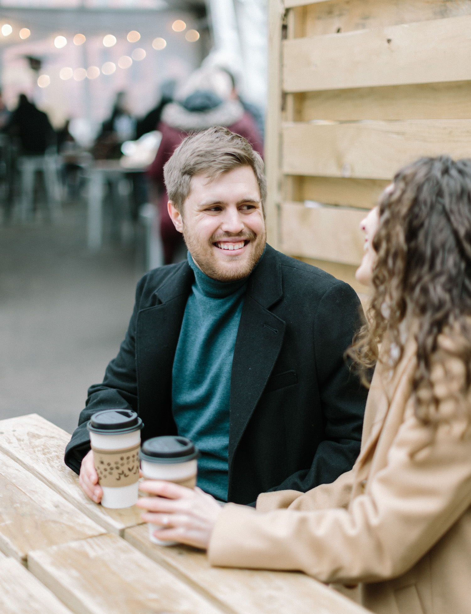 A man smiles at his fiancee during their coffee shop engagement photos in Detroit