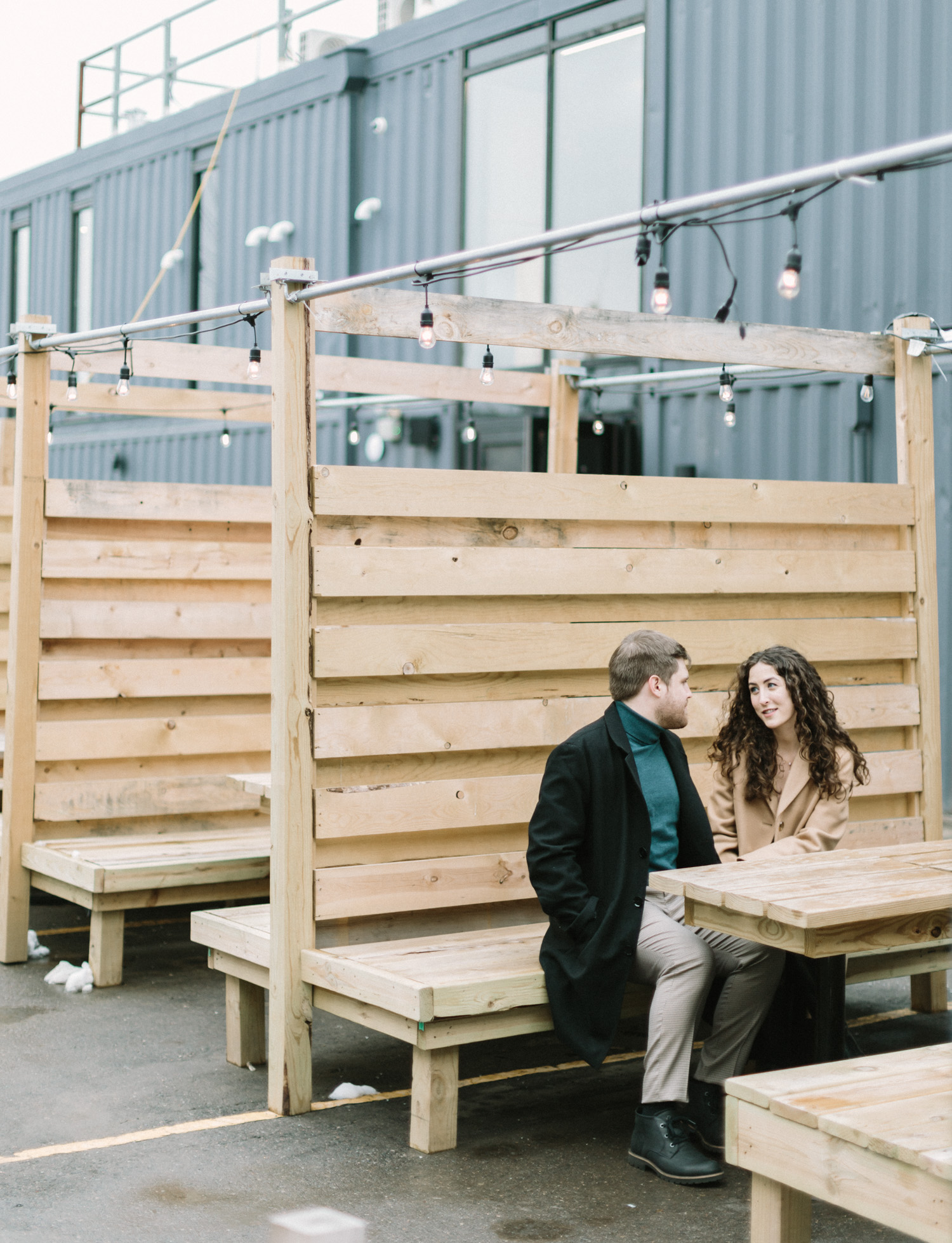 A couple sits outside with socially distanced seating for their Detroit engagement session