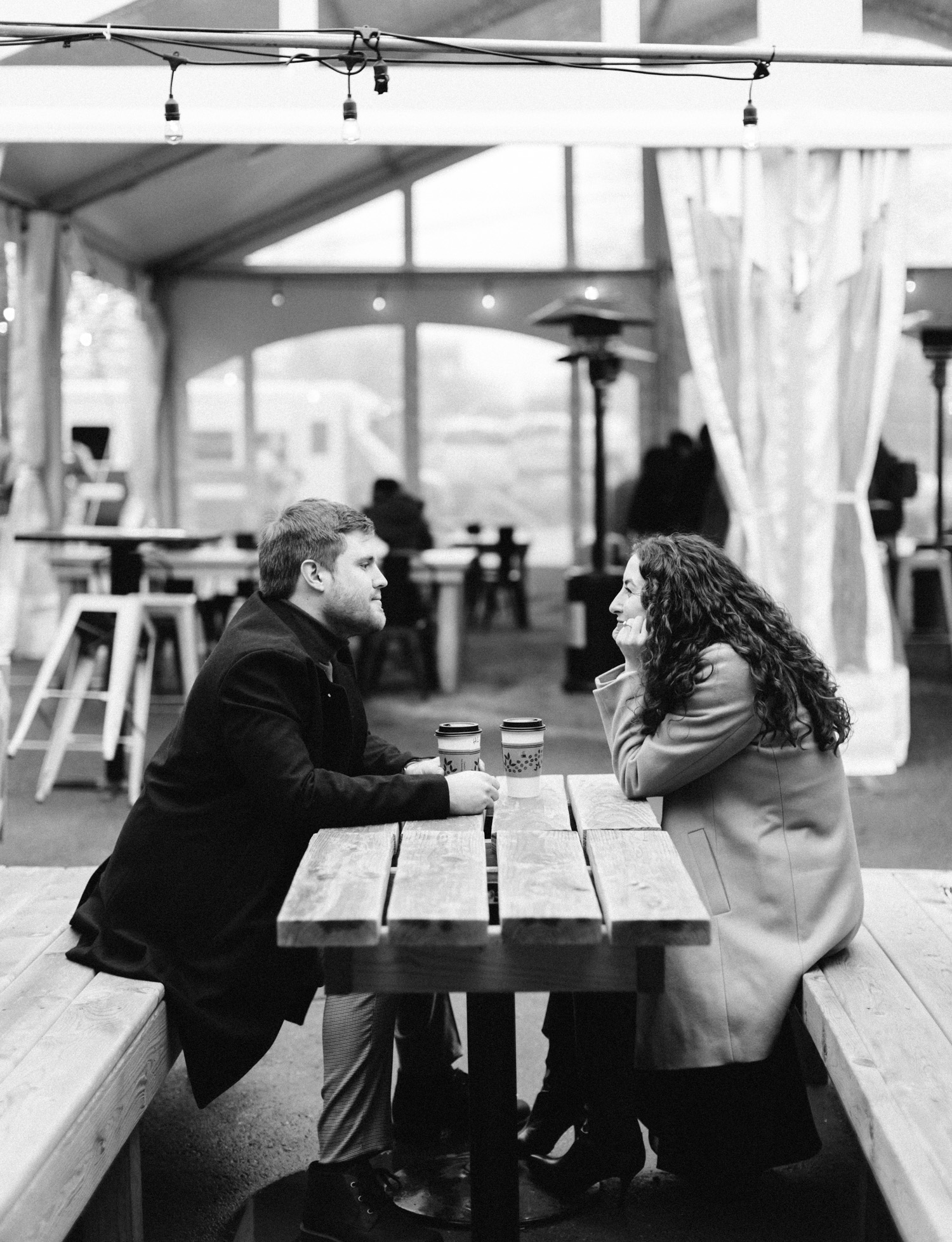 A timeless black and white engagement photo of a couple sharing coffee at Detroit Shipping Co. for their engagement session