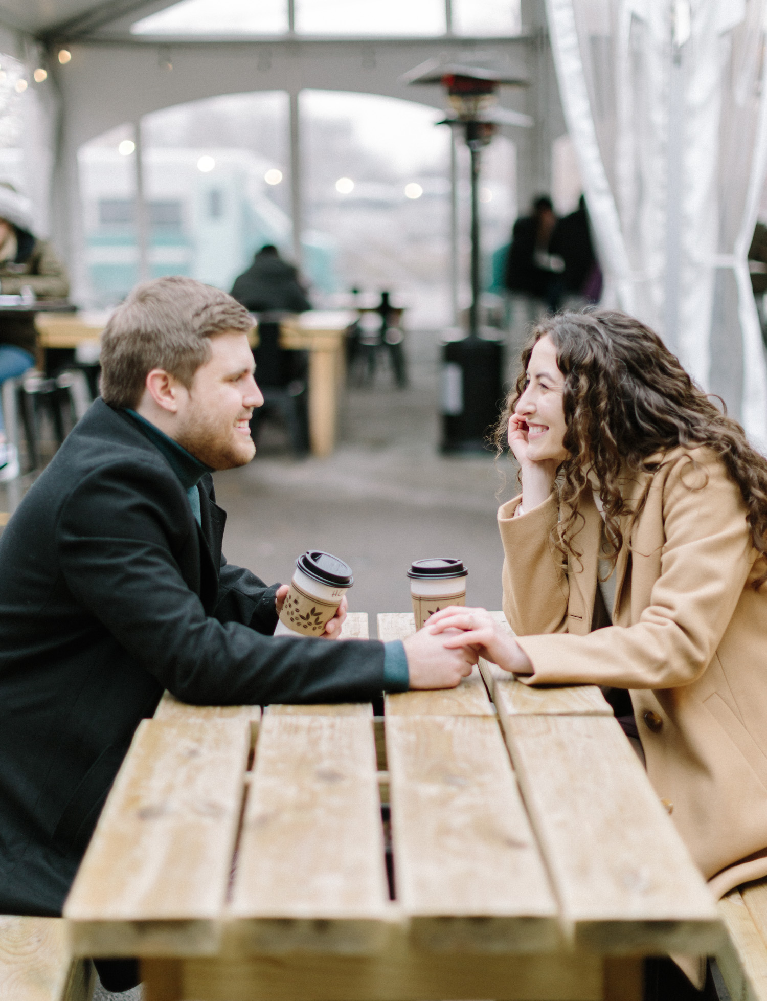 A couple leans in lovingly while sharing coffee at Detroit Shipping Co. during their engagement session