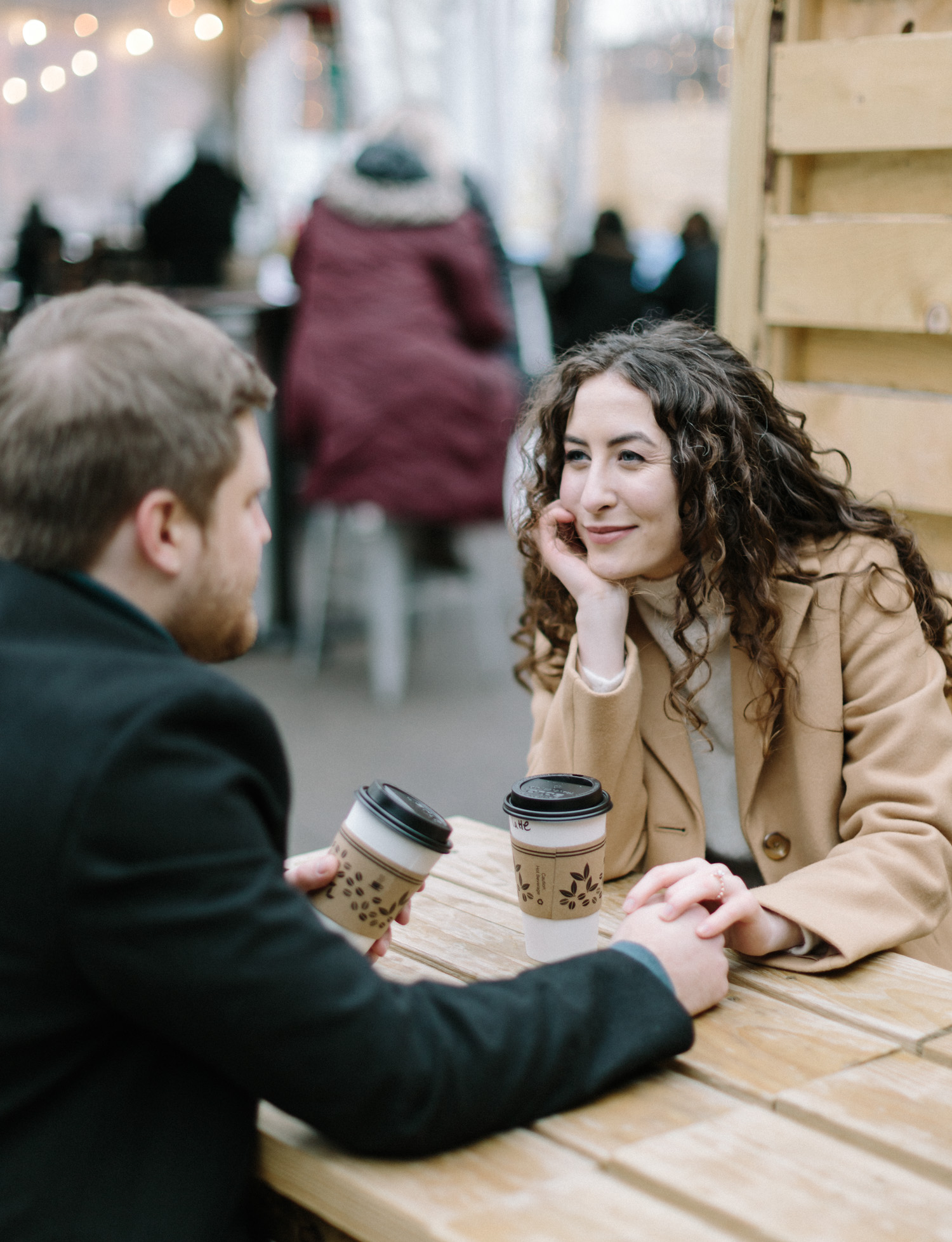 A couple talks while sharing coffee for their engagement photos in downtown Detroit