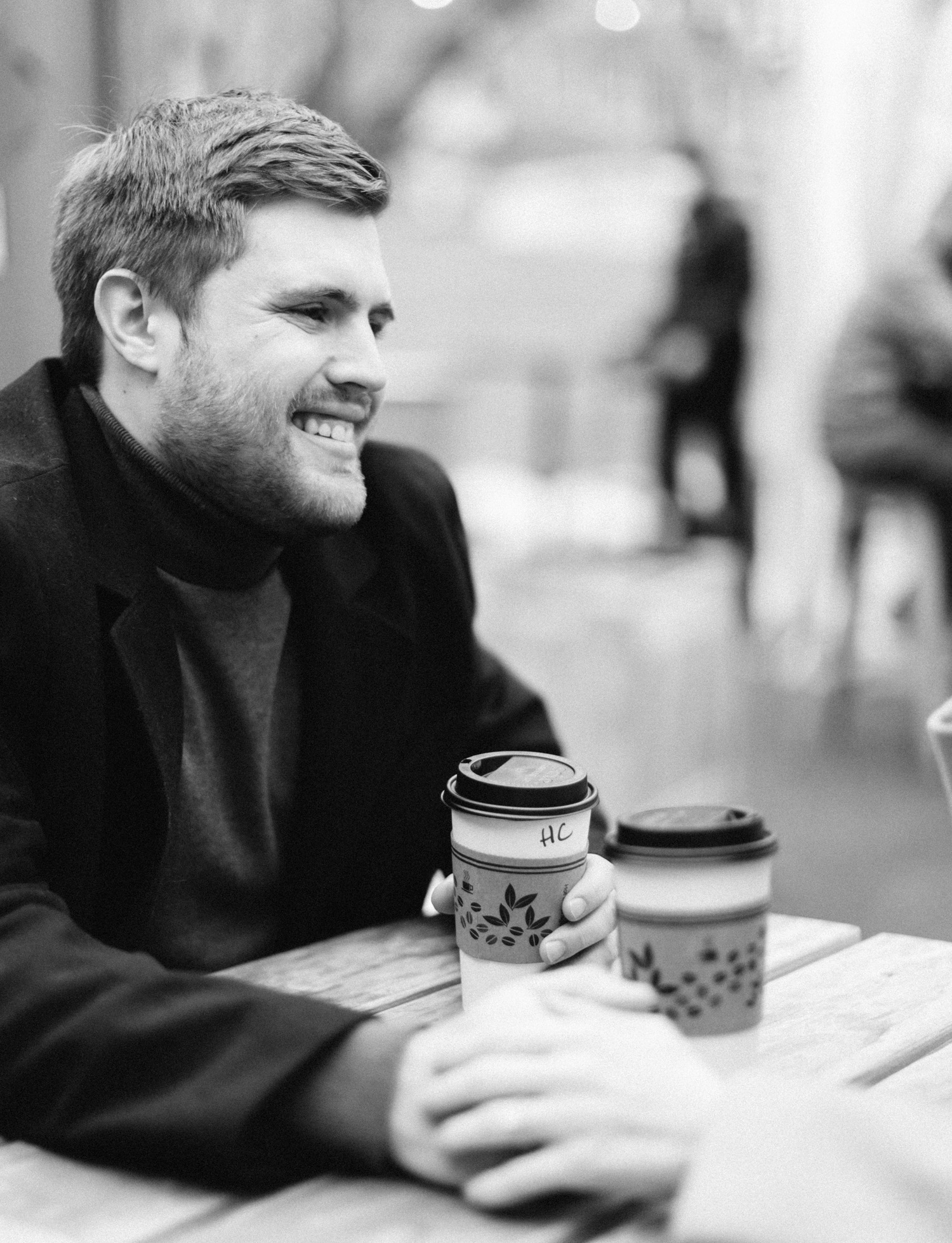 A man smiles at his woman while they share coffee during their Detroit engagement photos