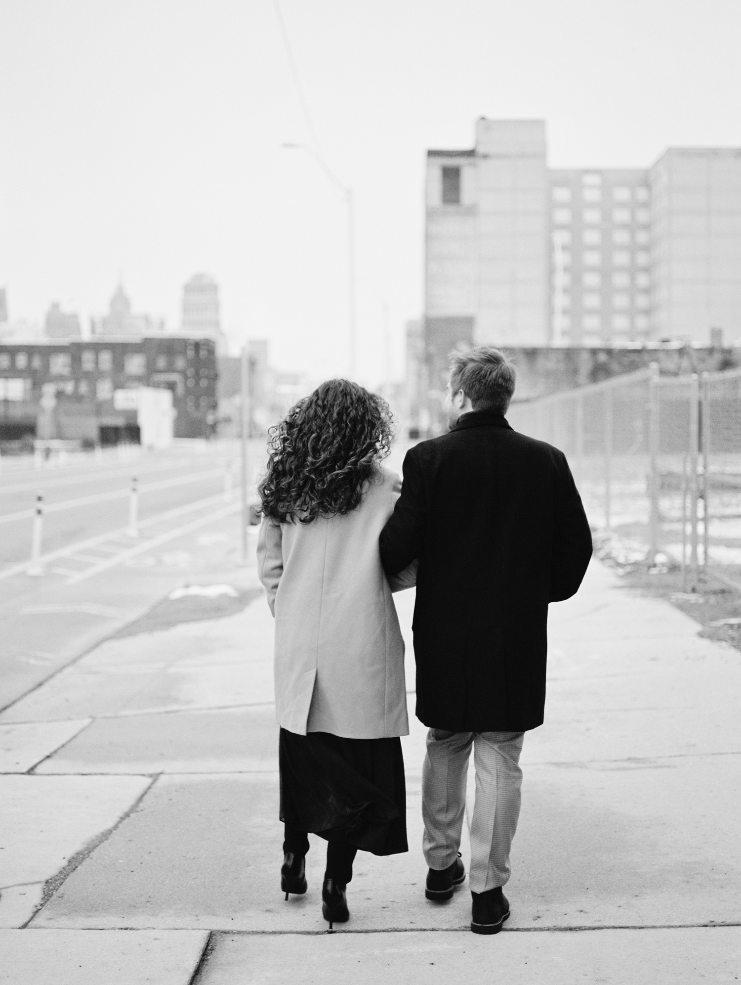 A couple walks down a street with the Detroit skyline ahead during their engagement photos