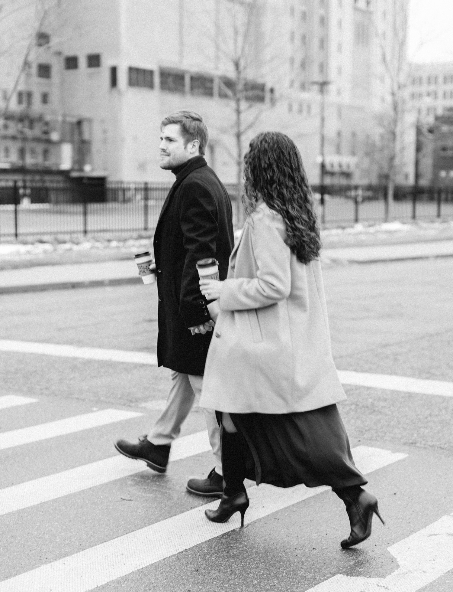 A couple crosses a Detroit street during their engagement photos, coffee in hand