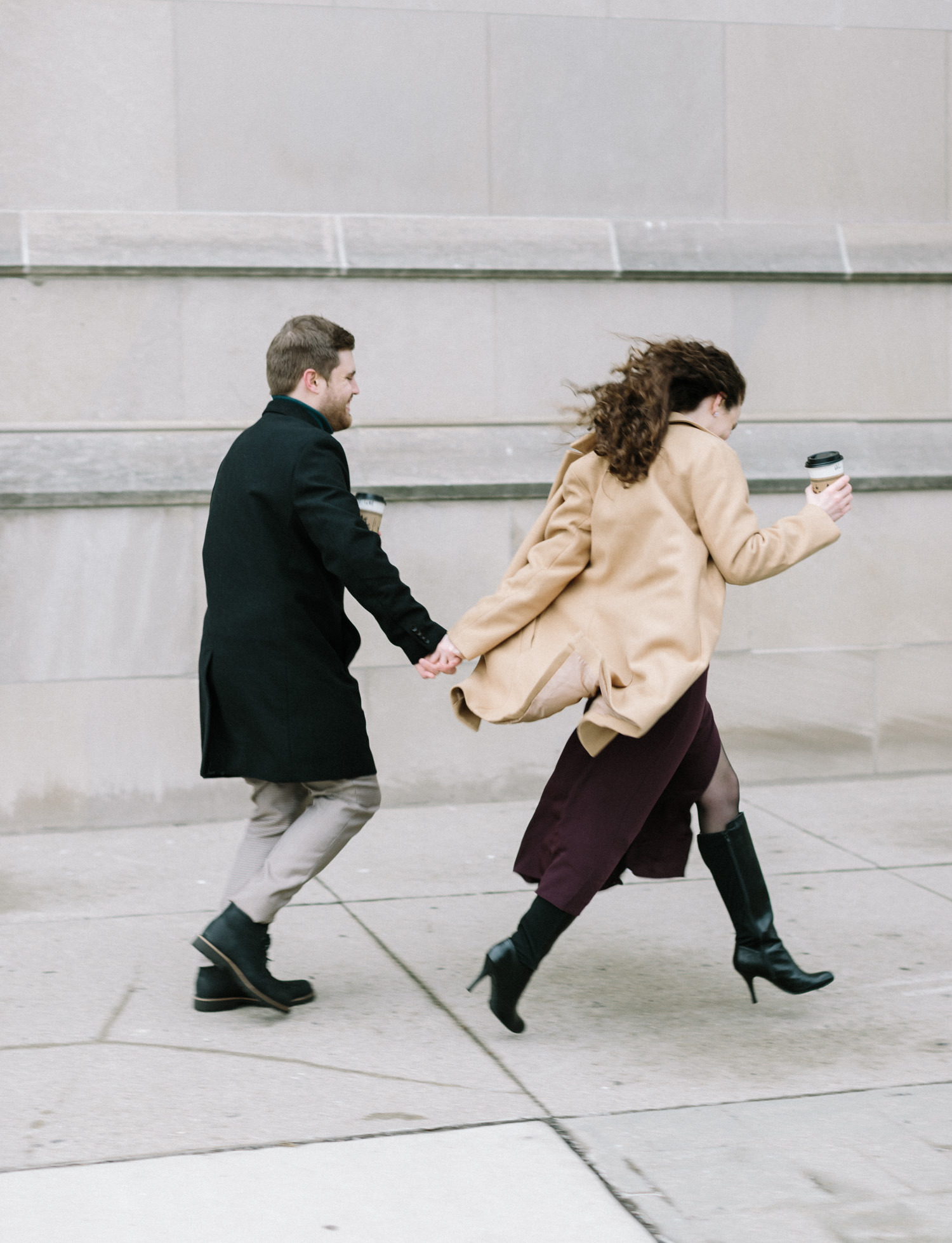 A couple runs down a Detroit street during their downtown engagement session
