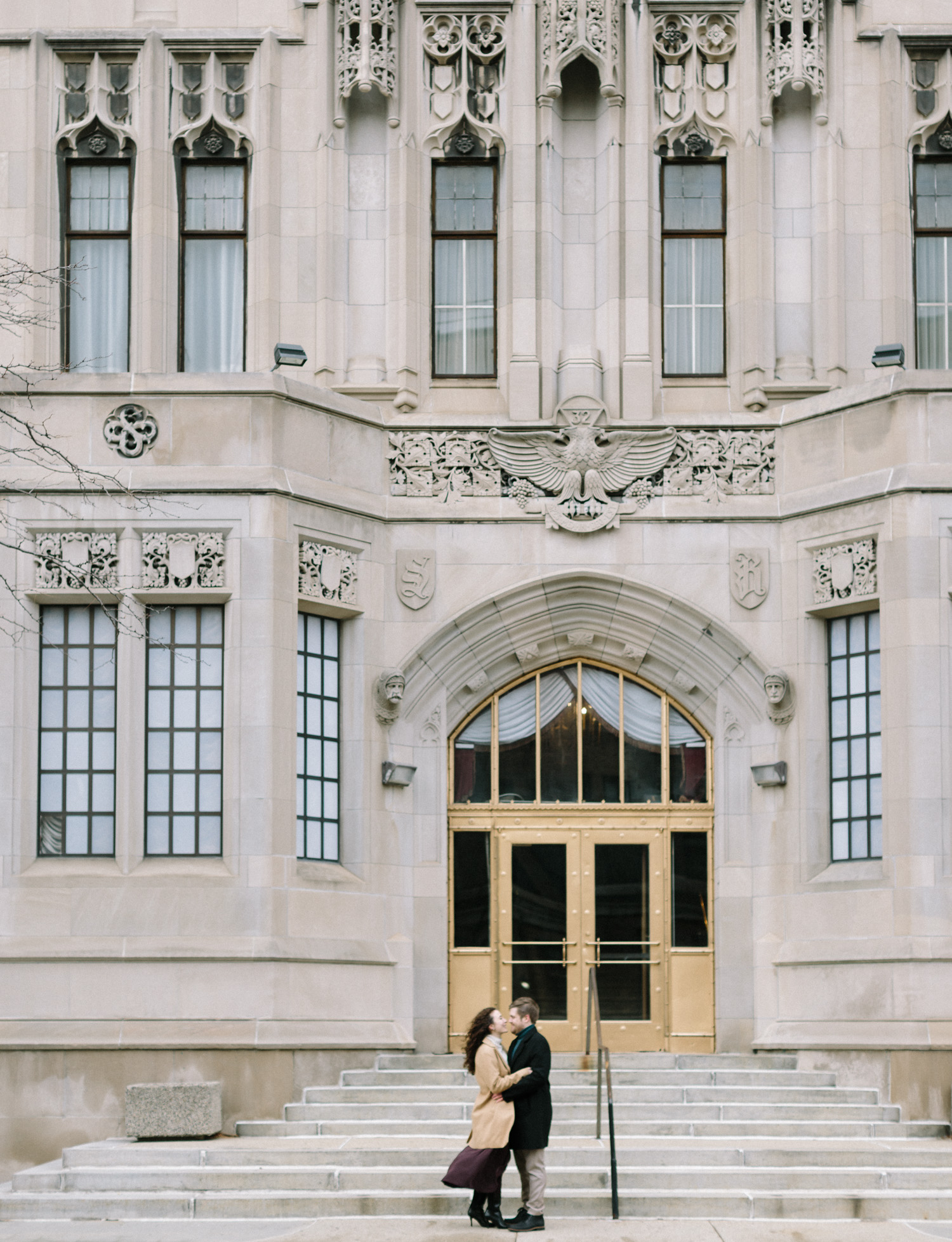 A couple embraces in front of the beautiful architecture of the Masonic temple in Detroit, Michigan