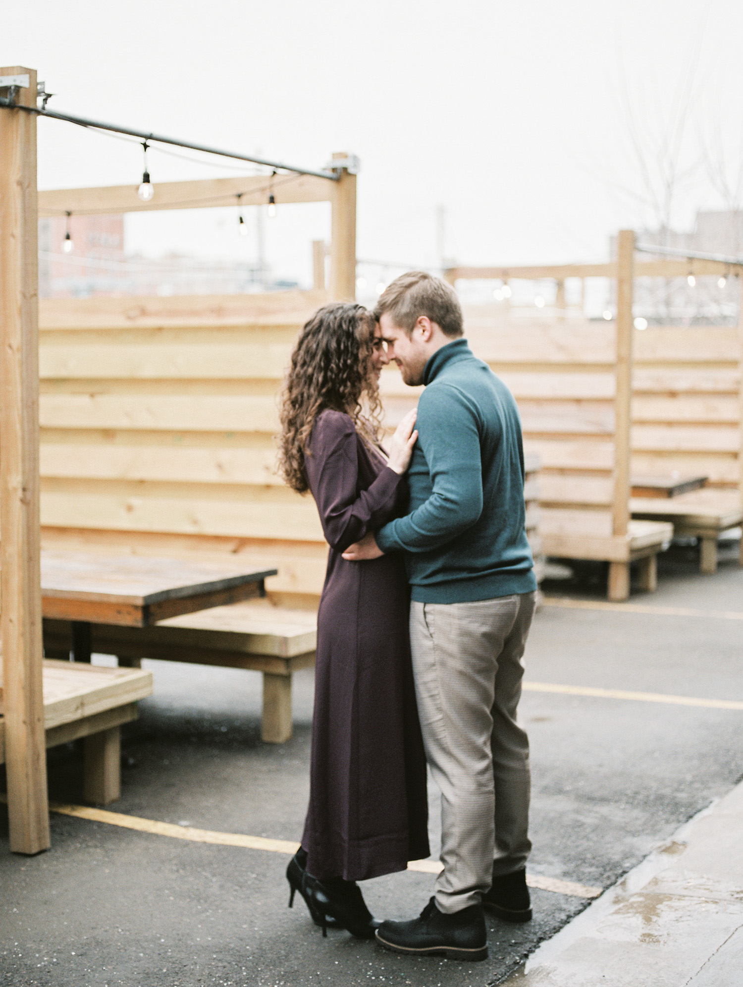 An engaged couple embraces at Detroit Shipipng Co. during their Michigan engagement session on film