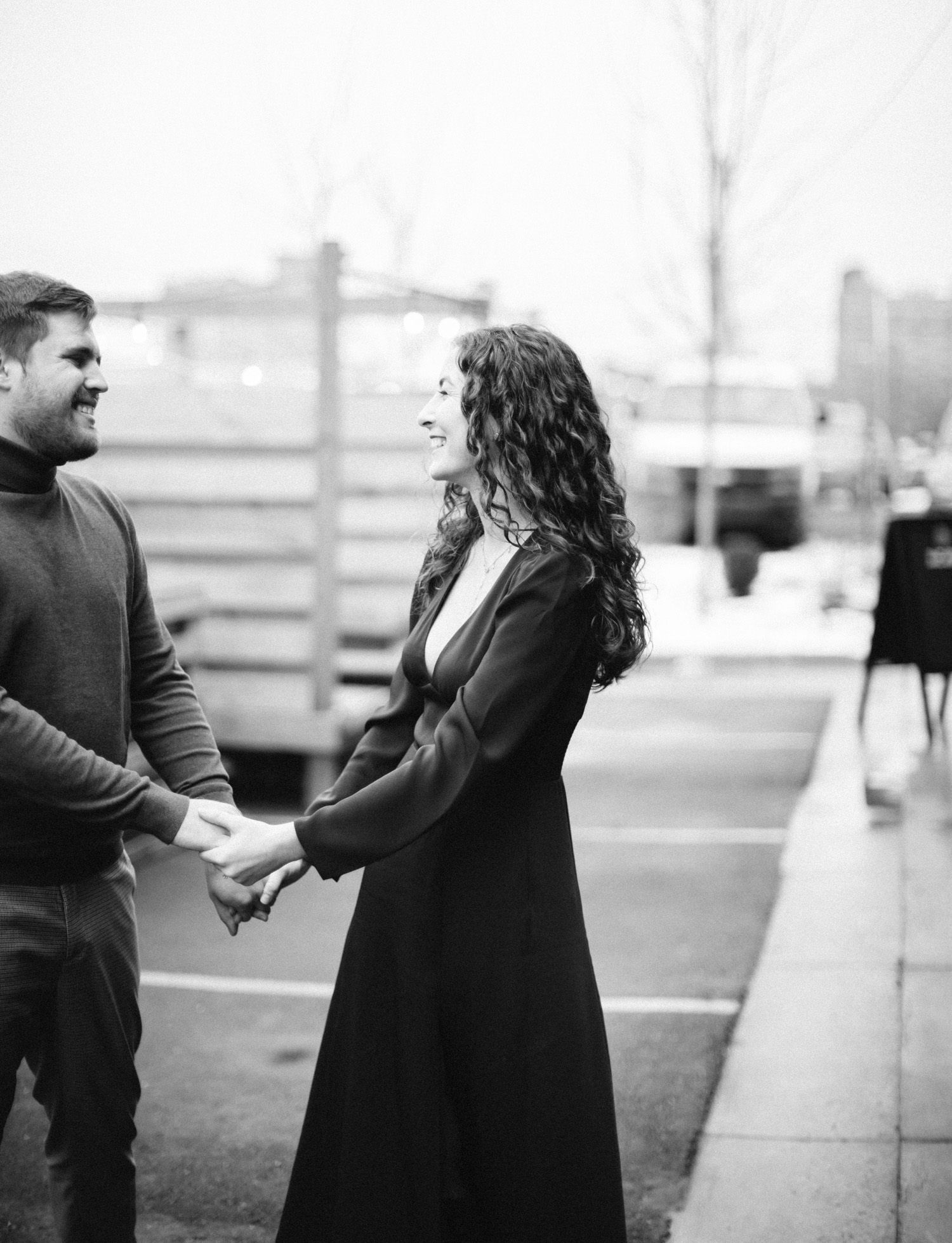 a couple dances playfully during their Detroit engagement photos in winter