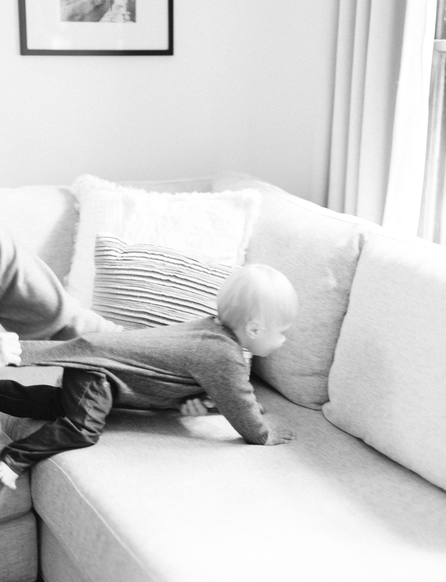 A mother holds his toddler's shirt while he attempts to escape across the couch at their Royal Oak home