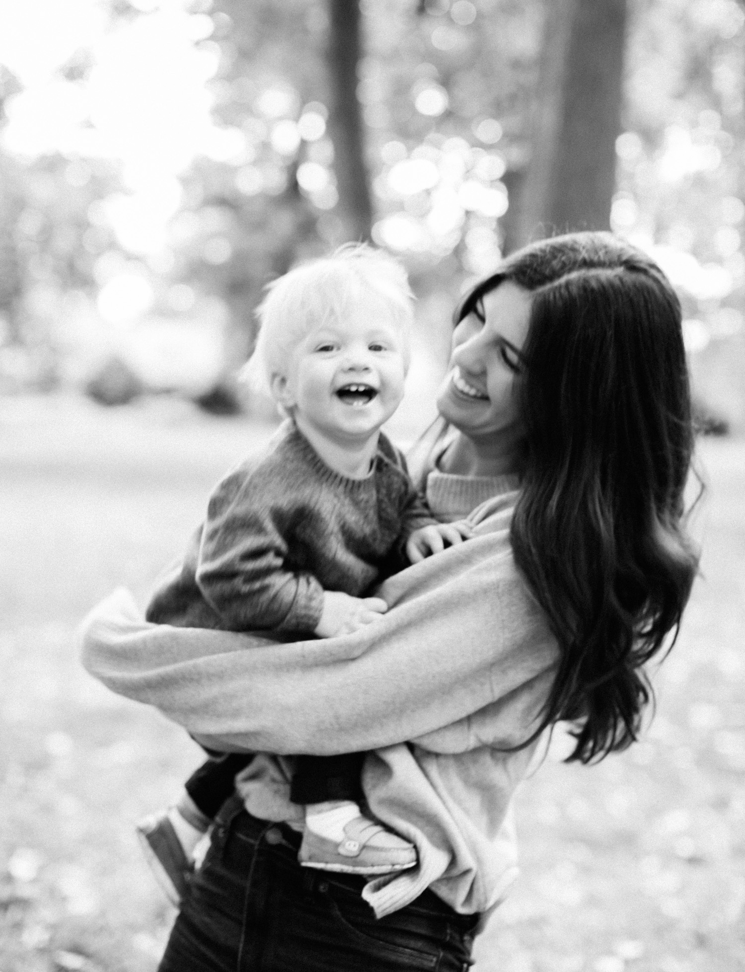A mother laughs while holding her blonde toddler son during their natural, lifestyle family photos on film in Royal Oak, Michigan