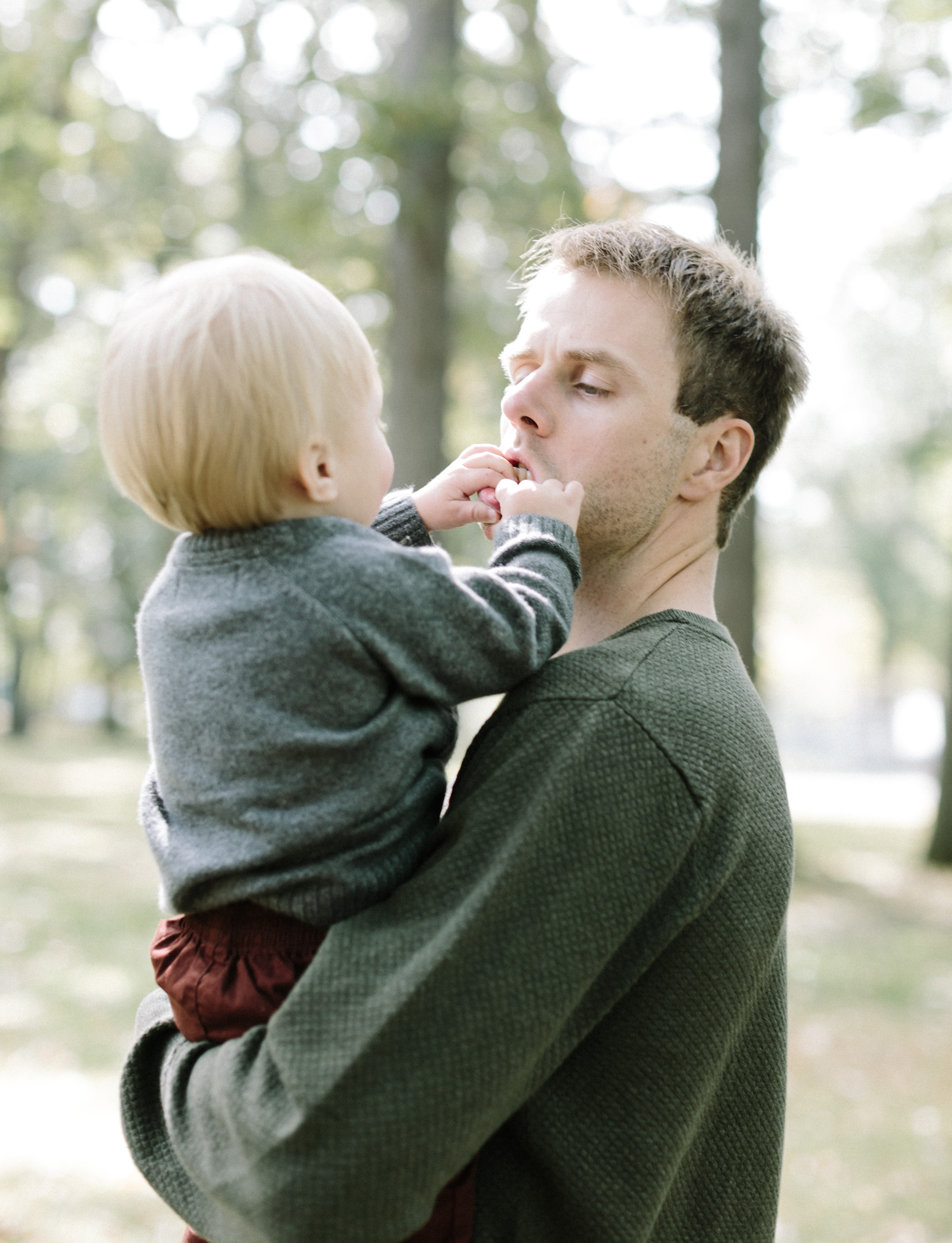 A son pulls playfully on his dad's lips while he holds him at a park in Royal Oak, Michigan