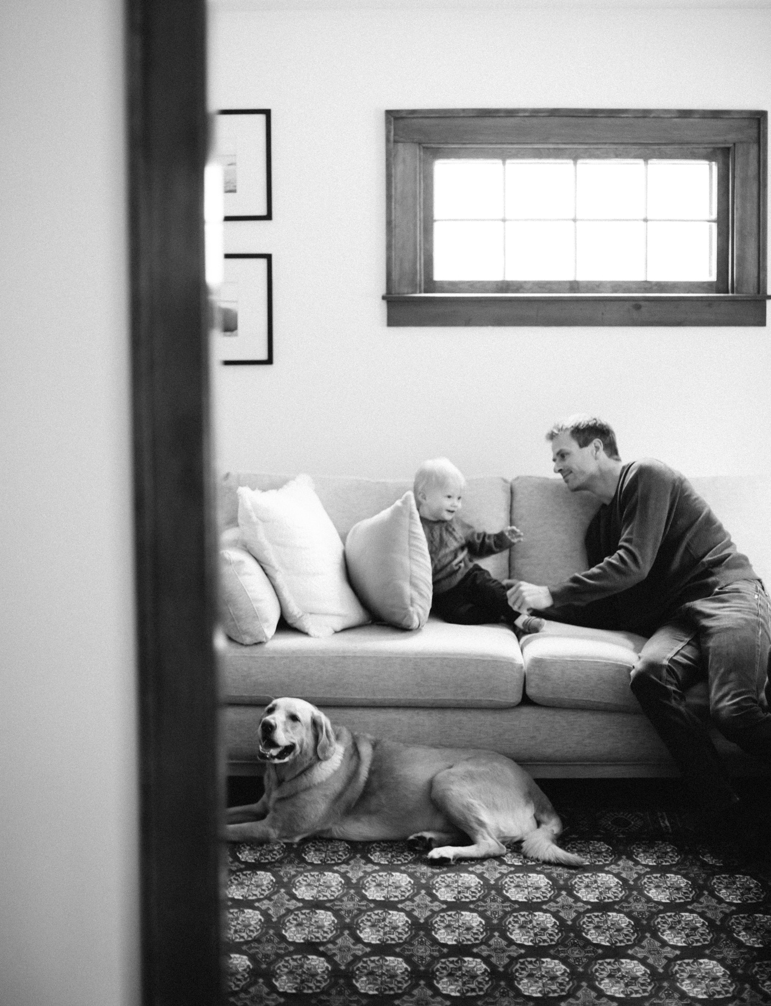 A black and white image of a father, son, and dog resting and playing on the living room couch is captured during natural lifestyle family photography in Royal Oak, Michigan