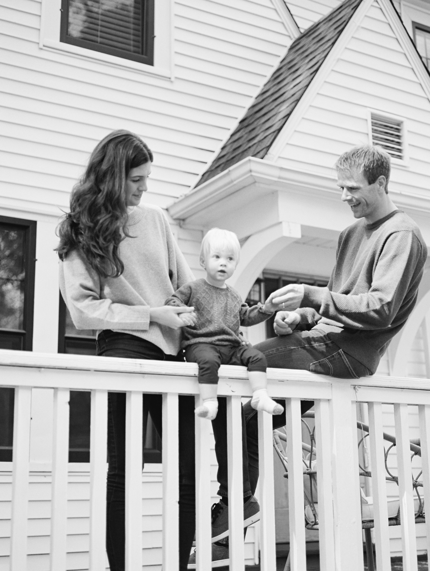 A timeless black and white family photo of a family on the porch of their Royal Oak, Michigan home