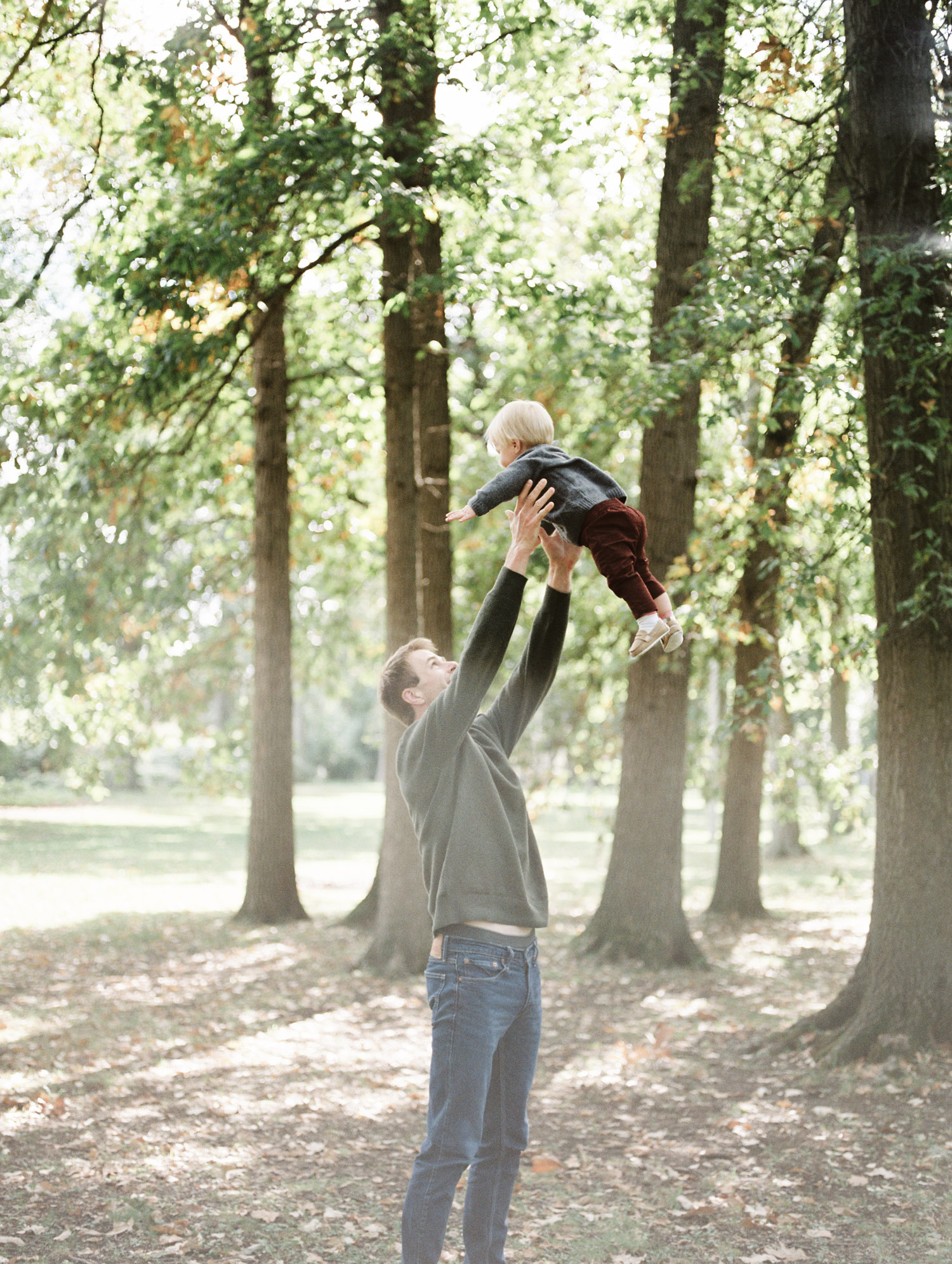 A father tosses his toddler son in the air at a park in Royal Oak as the fall leaves begin to turn