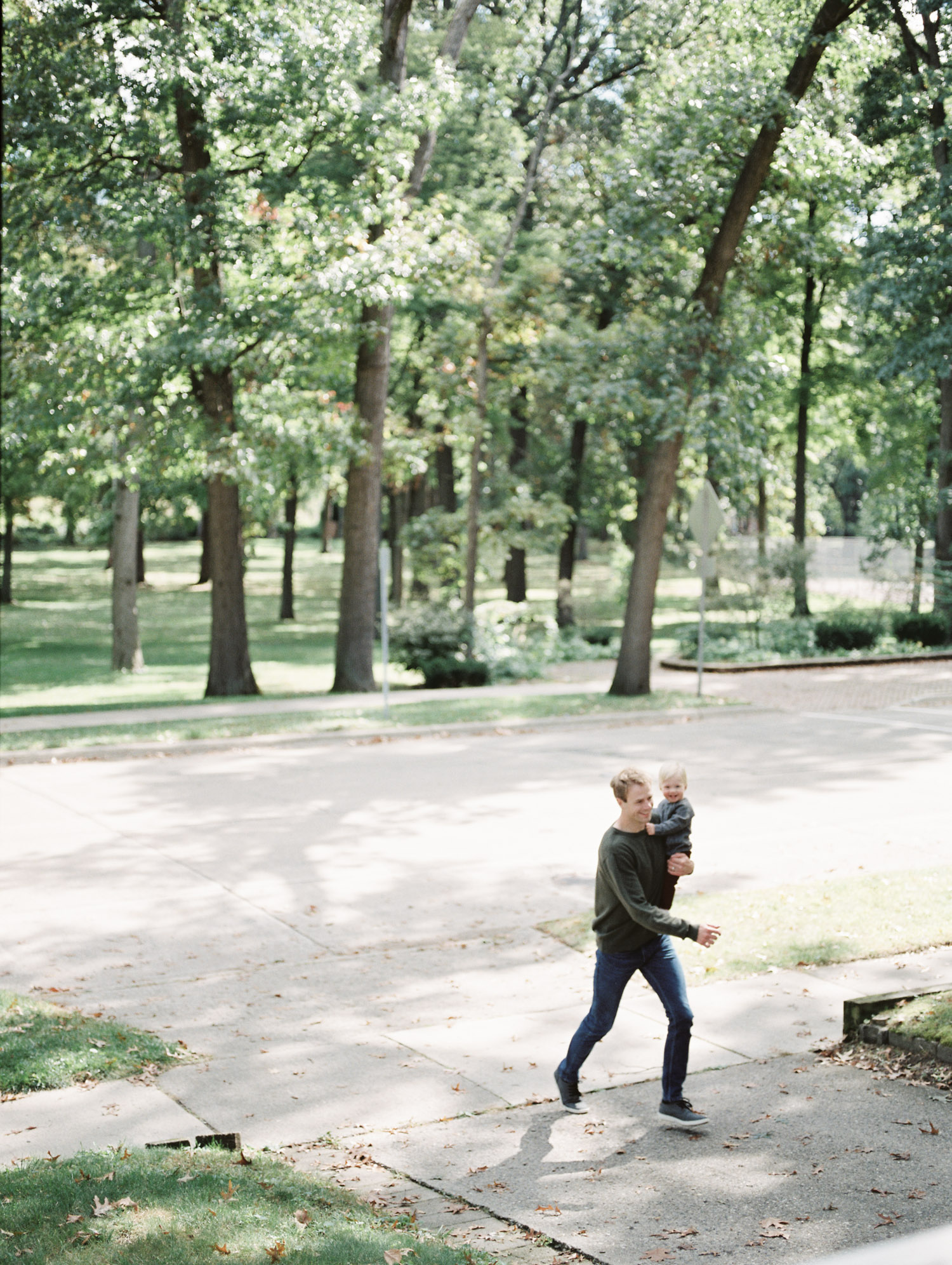 A father walks up the driveway with his toddler son during lifestyle family photos in Royal Oak, Michigan