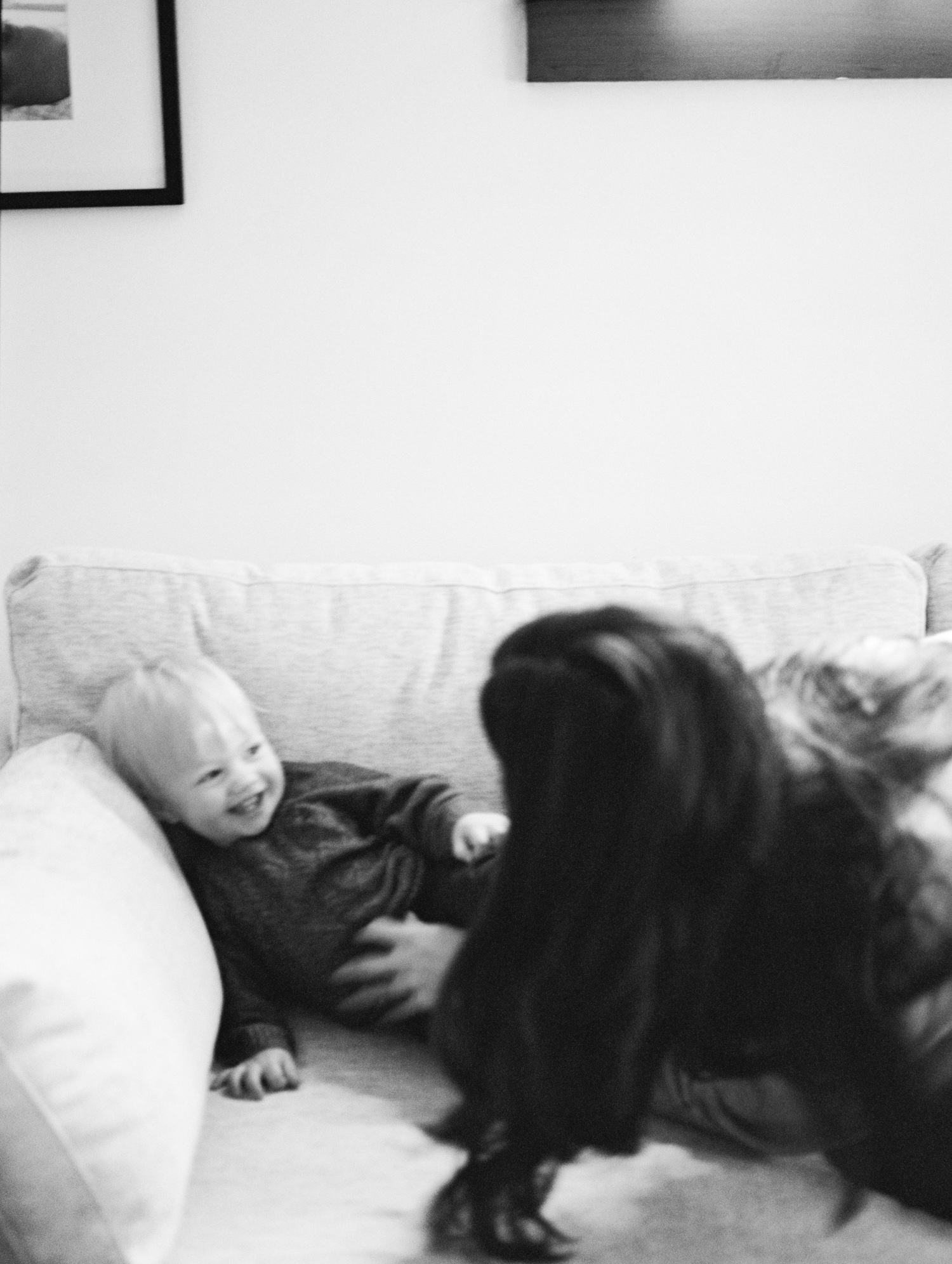A mother tickles her son on their couch during their at home family photos in Royal Oak